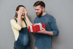 Pregnant woman with eyes closed taking gift from her husband royalty free stock photos