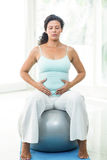 Pregnant woman with eyes closed touching her belly while sitting on ball Royalty Free Stock Image