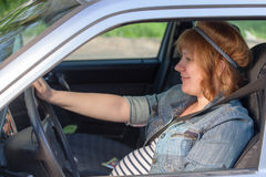 Pregnant woman fastening seat belt in car Stock Photos