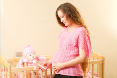 Pregnant woman feeding from  bottle toy Teddy bear Stock Image