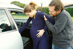 Pregnant woman feeling pain helped to get into car by boyfriend Royalty Free Stock Photography