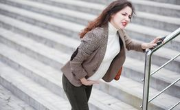 A pregnant woman feels pain on the street stock photo