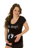 Pregnant woman with feet on shirt smile Royalty Free Stock Images