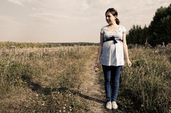 Pregnant woman in field with a bunch of wild flowers under belly royalty free stock photography