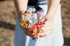 Pregnant woman in field with a bunch of wild flowers under belly stock photos