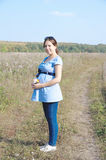 Pregnant woman in field with a bunch of wild flowers under belly Stock Photography
