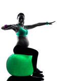 Pregnant woman fitness exercises silhouette. One caucasian pregnant woman exercising fitness exercises in silhouette studio isolated on white background royalty free stock photography