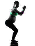 Pregnant woman fitness exercises silhouette. One caucasian pregnant woman exercising fitness exercises in silhouette studio isolated on white background royalty free stock photo