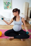 Pregnant woman during fitness workout Stock Photos