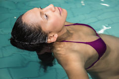 Pregnant woman floating in the pool Royalty Free Stock Photos