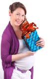 Pregnant woman with flower in hair hugs box with gift Royalty Free Stock Photography