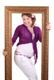 Pregnant woman with flower in hair poses in frame Stock Images