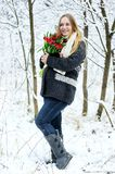 Pregnant woman with flowers in winter forest Royalty Free Stock Photo