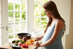 Pregnant Woman Following Recipe On Digital Tablet Royalty Free Stock Image