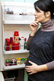 Pregnant woman and fridge. Pregnant woman standing at open fridge, wondering what to eat stock images