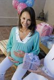 Pregnant Woman And Friend At A Baby Shower. Portrait of happy pregnant women with friend holding gift at a baby shower stock photo