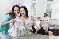 Pregnant Woman And Friend Holding Baby Clothes Royalty Free Stock Photography