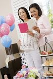 Pregnant Woman And Friend Reading Greeting Card Royalty Free Stock Photo