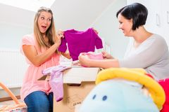 Pregnant woman and friend sharing baby clothes. Soon-to-be mums choosing babywear for neonates royalty free stock photos