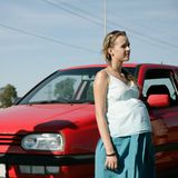 Pregnant woman in front of car. Pregnant woman standing in front of red car Stock Photos