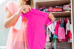 Pregnant woman in front of wardrobe in childs room. Soon-to-be mom shows girls clothes with anticipation in baby room Stock Photography