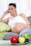 Pregnant woman with fruit on table Royalty Free Stock Photo