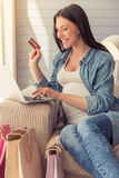 Pregnant woman with gadget. Beautiful pregnant woman is holding a credit card, using a laptop and smiling while doing shopping online Stock Photo
