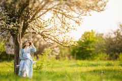 Pregnant woman in the garden. Pregnant woman in the blossom garden on the swing Royalty Free Stock Photography