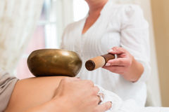 Pregnant woman getting sound bowl treatment. Pregnant women getting sound bowl wellness treatment Stock Photos