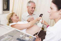 Pregnant woman getting ultrasound from doctor royalty free stock photos