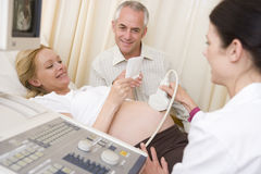 Pregnant woman getting ultrasound with husband royalty free stock images