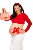 Pregnant woman with gift. Beauty pregnant woman with red bow showing gift bag isolated on white background royalty free stock images