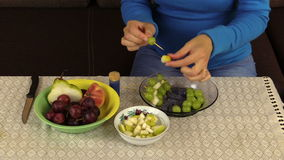 Pregnant woman girl prepare dessert from grapes and fruit pieces stock footage
