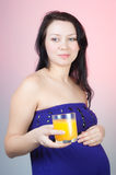 Pregnant woman with a glass of orange juice royalty free stock photo