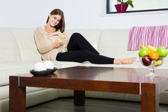 Pregnant woman with glass of water. On couch Royalty Free Stock Image