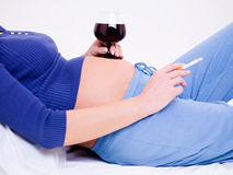 Pregnant woman with a glass of wine Stock Images