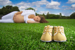 Pregnant Woman. On the grass, looking on the shoes of her baby Stock Image