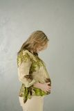 Pregnant woman with green blouse holding belly. Pregnant woman wearing green blouse holding belly with grey packground, profile Stock Images