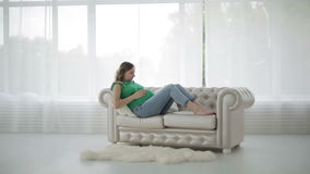 A pregnant woman in a green blouse is sitting on the sofa and stroking big belly. The woman is relaxing lying on the couch in a big bright room stock video