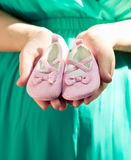 Pregnant woman in green dress belly holding pink baby booties, e. Xpecting girl. Healthy pregnancy Royalty Free Stock Photos