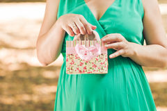 Pregnant woman in green dress pulls out a pink baby booties from. A package in the autumn park. Close Up Stock Images