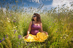 Pregnant woman on green grass field under blue sky Stock Images