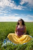 Pregnant woman on green grass field under blue sky Royalty Free Stock Photography