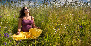 Pregnant woman on green grass field under blue sky Stock Image