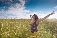 Pregnant woman on green grass field under blue sky Royalty Free Stock Image