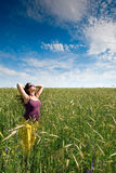 Pregnant woman on green grass field under blue sky. In summer Stock Photo