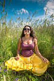 Pregnant woman on green grass field under blue sky Stock Photo