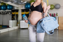 Pregnant woman at the gym holding sport bag and bidon Stock Image