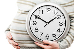 Pregnant woman hand holding large office wall clock showing time Royalty Free Stock Images