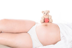 Pregnant woman with hands and have bear doll Stock Image